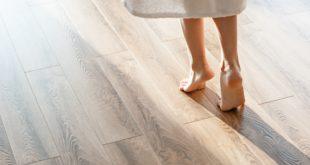 ogrzewanie podłogowe kobieta w szlafroku chodząca na bosaka po drewnianej podłodze