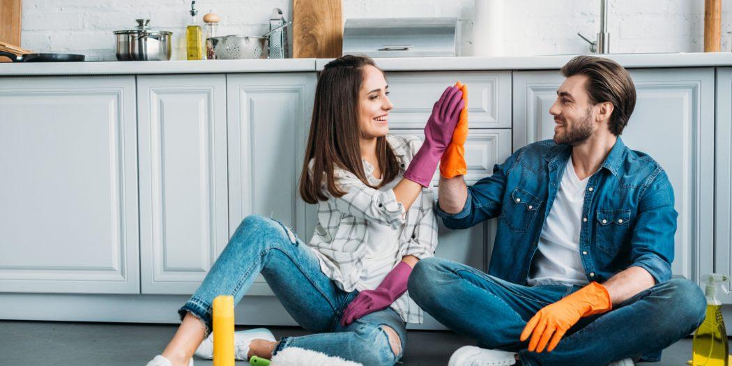 para siedząca na podłodze i przybijająca sobie piątke w rękawicach do sprzątania