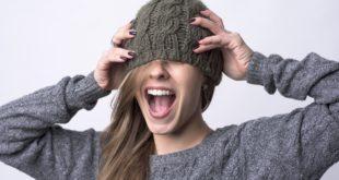 uśmiechnięta dziewczyna z długimi włosami w wełnianej szarej czapce