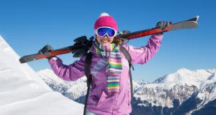 dziewczyna w różowej kurtce na stoku narciarskim z nartami na plecach