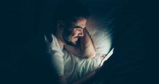 mężczyzna wpatrzony nocą w ekran smartfona