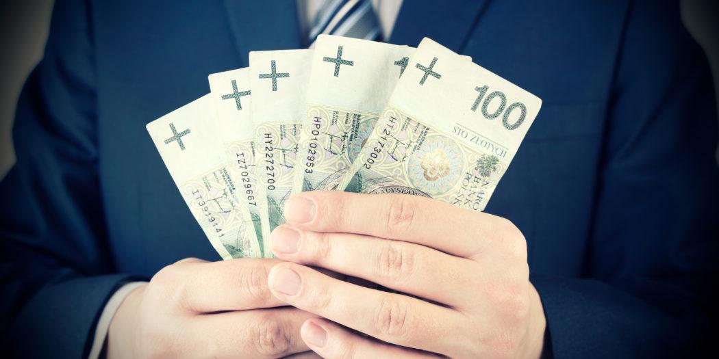 biznesmen trzymający w dłoni plik banknotów 100 złotych PLN