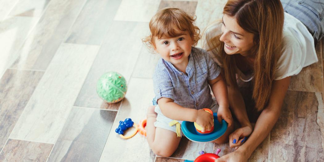 Mama bawiąca sie z dwulatkiem na podłodze