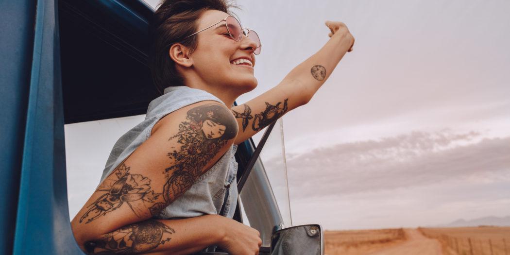 młoda dziewczyna z tatuażami podróżująca samochodem