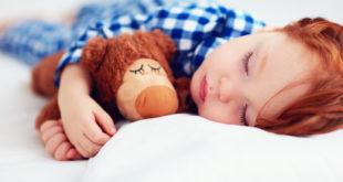 urocze rudowłose dziecko śpiące z maskotką