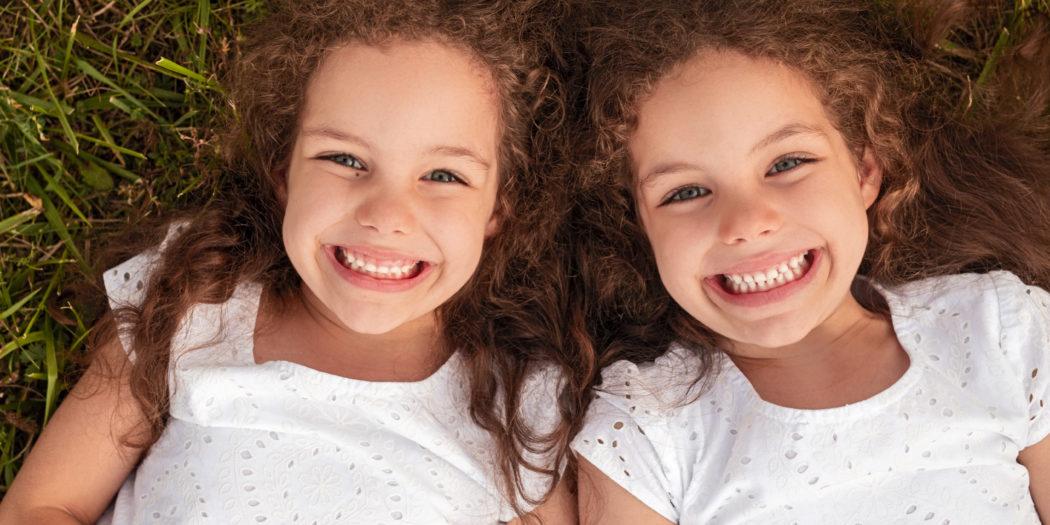 dwie śliczne dziewczynki bliźniaczki na trawie