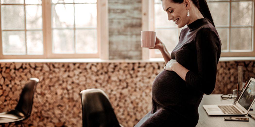 kobieta w ciąży spoglądająca na swój brzuch