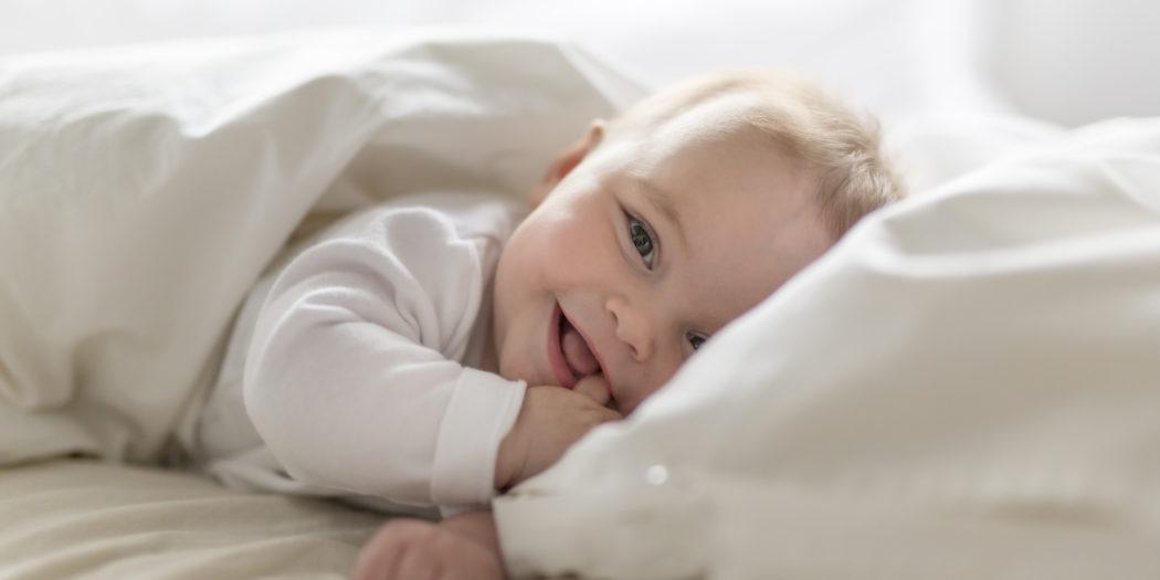 zadowolone dziecko w białej pościeli