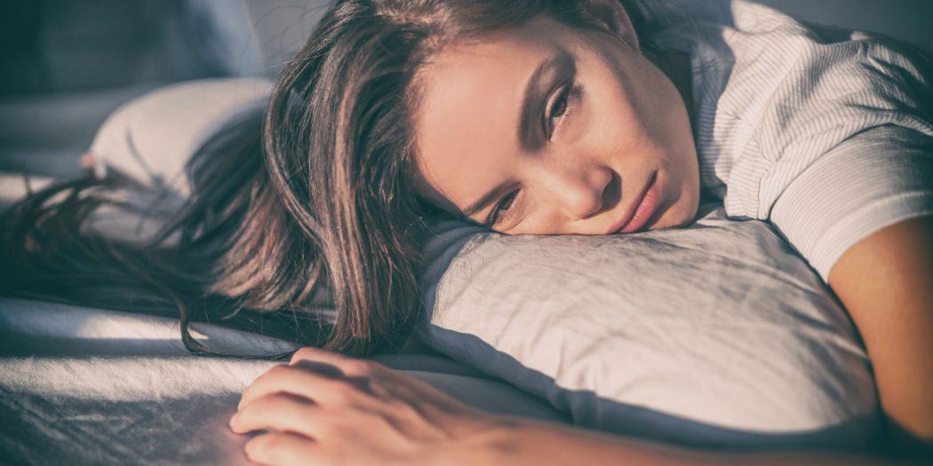 smutna i zmęczona dziewczyna w pościeli