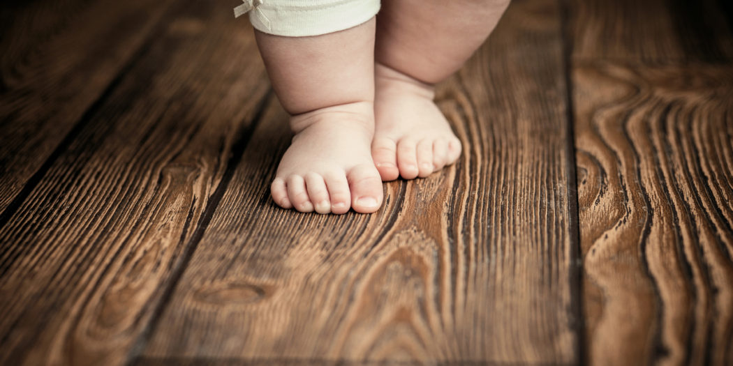 dziecięce stopy na drewnianej podłodze