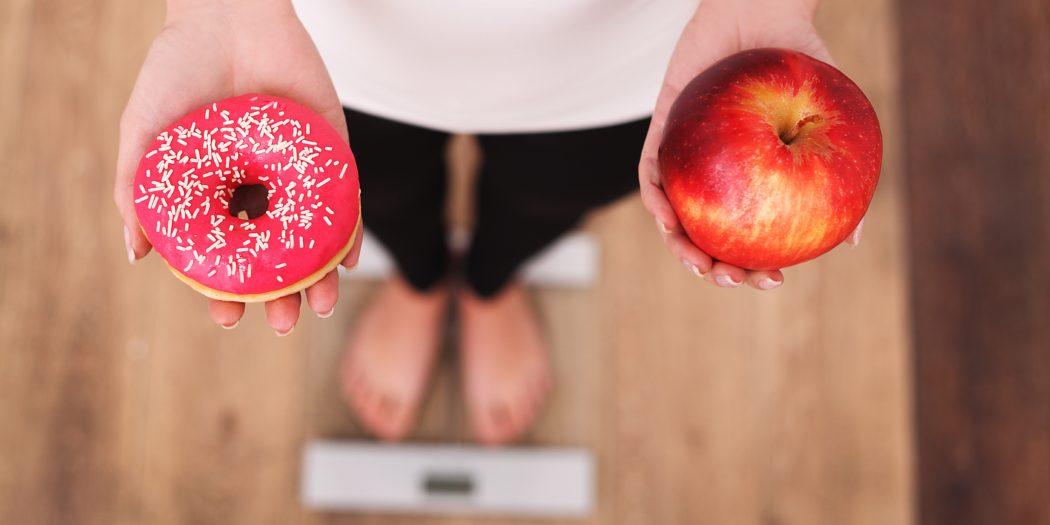 kobieta na wadze wybór między pączkiem a jabłkiem