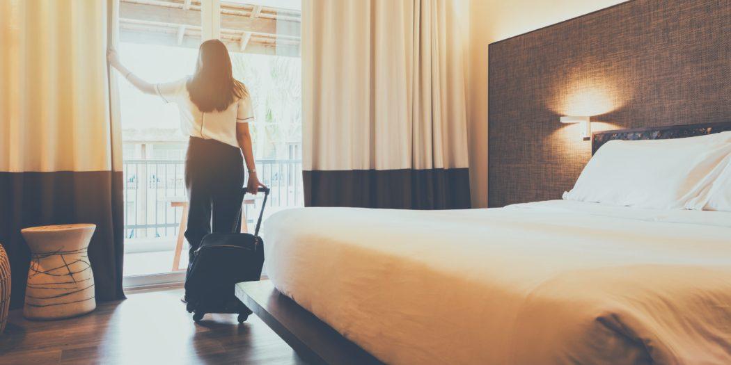 młoda kobieta z walizką w pokoju hotelowym