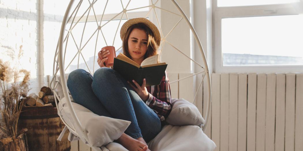 zrelaksowana kobieta czytająca książkę latem na huśtawce