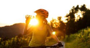 kobieta na rowerze pijąca wode z bidonu
