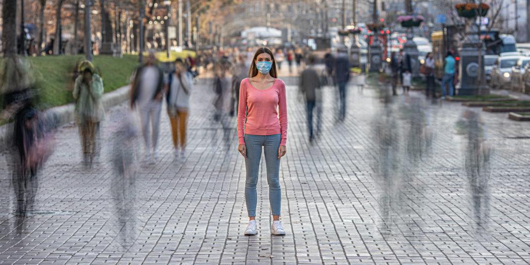 kobieta w maseczce na ulicy na tle rozmytego tłumu