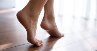 kobiece bose stopy na drewnianej podłodze