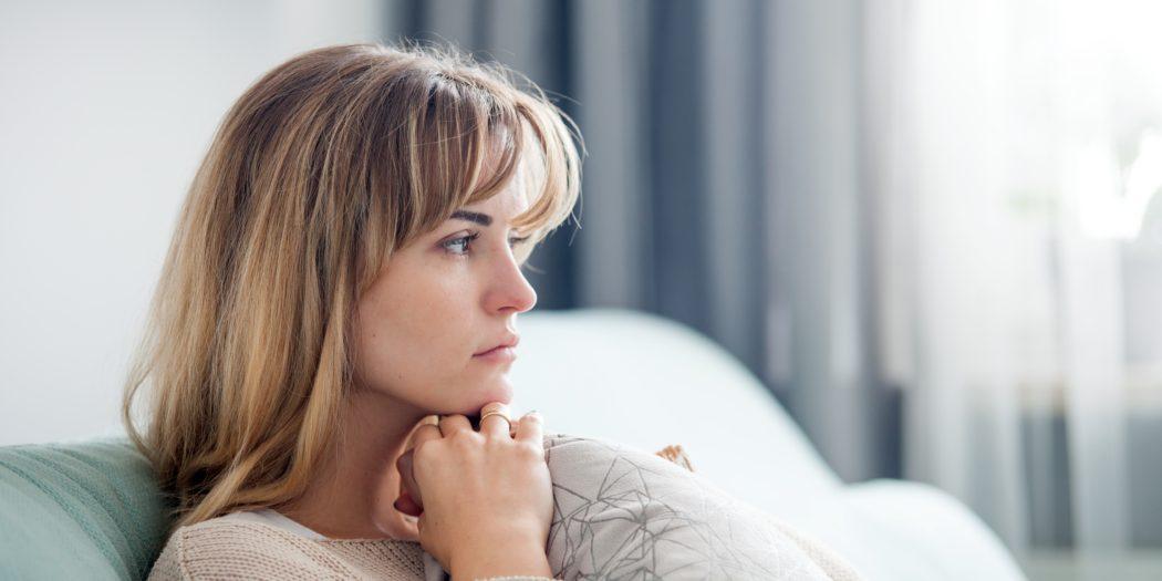 smutna kobieta siedząca na kanapie
