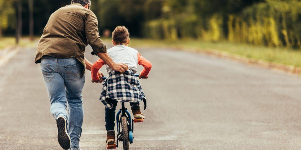 rodzic uczący dziecko jazdy na rowerze