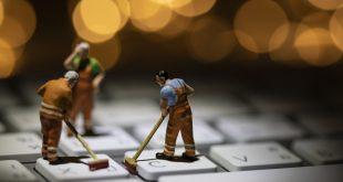 ludziki sprzątające klawiaturę komputera